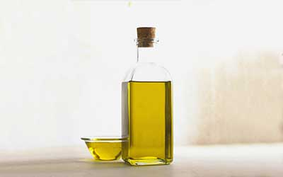 bottle with cork stopper next to a glass bowl both filled with olive oil.