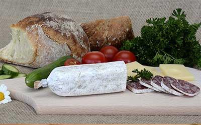 fuet cortado sobre una tabla con junto a pan y tomate y queso.
