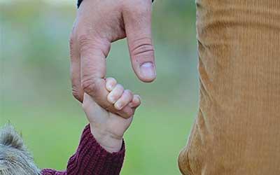 categoria dettagli festa del papà, si può vedere la mano di un padre che tiene la figlia.