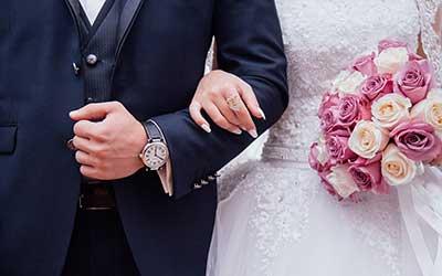 categoria dettagli matrimonio, si vedono uno sposo e una sposa a braccetto.