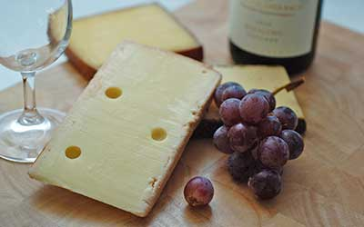 cheese board next to grapes and wine