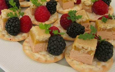 pieces of paté with blackberry and raspberry on salted biscuit.