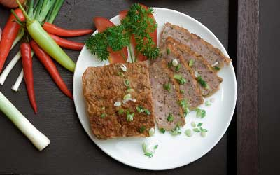 block of pate with vegetables on a plate.
