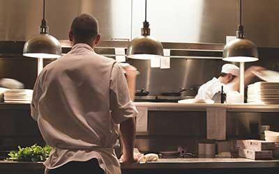 cocina de restaurante con dos cocineros trabajando.